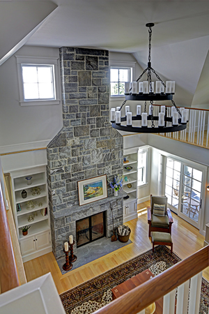 Interior design looking down on fieldstone fireplace from second story landing Cushing, Maine home by Phelps Architects.