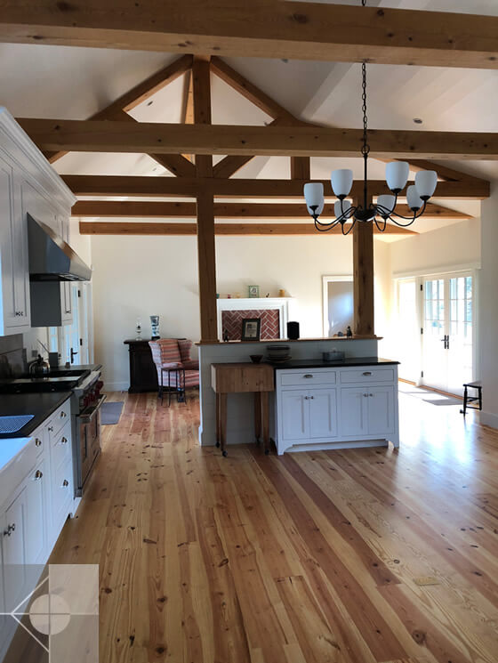 A new farm-house style kitchen and great room feature with exposed structural pine truss and cathedral ceiling designed by Phelps Architects.